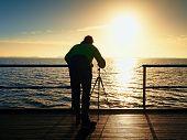 Постер, плакат: Man Photograph With Camera On Tripod Tourist At Handrail On Mole