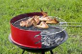 stock photo of chicken wings  - Chicken wings grilling in the red barbecue - JPG