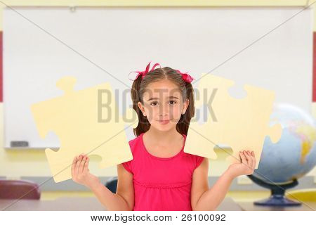 Beautiful 7 year old girl holding two large puzzle pieces in school classroom.