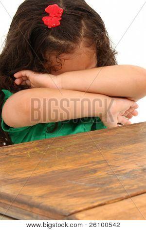 Sad little three year old hispanic girl sitting in big desk over white background.