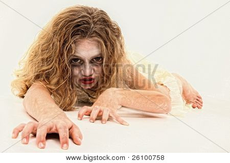 Adorable 7 year old girl in Zombie costume over white background.