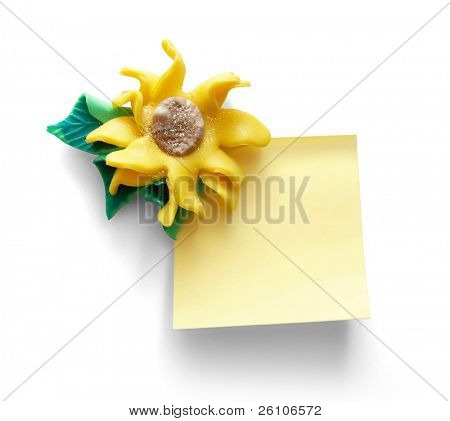 Yellow note paper with artificial flower on it. Isolated on white. Closeup.