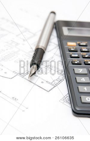 Calculator with fountain pen on house plan blueprint. Closeup.