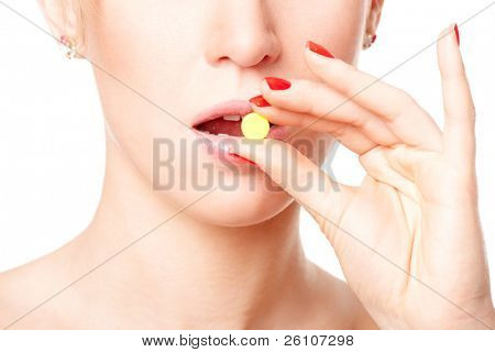 Young woman taking yellow pill. Isolated on white. Closeup.