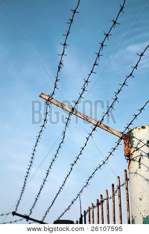 Barbed wire against a blue sky with cirrus clouds. With part of metal fence.