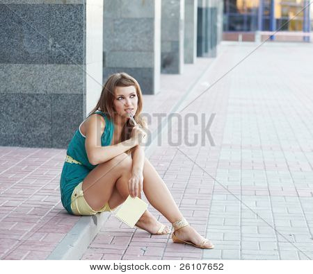 Cute student teenage girl sitting at dreaming at urban scene. With notebook and pen. She is positive.