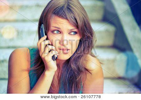 attraktive Teenager mit Problemen per Telefon sprechen. Sie sorgen, und sie ist frustriert.