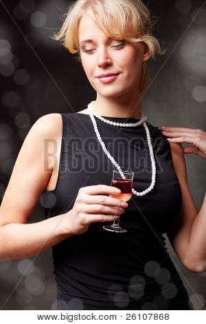 Portrait of a sexy girl in evening dress holding a glass of wine. On dark background with blurry lights.
