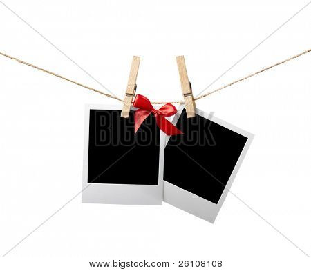Two blank instant photos with red bow hanging on the clothesline. Isolated on white.