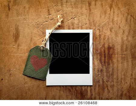 Blank instant photo frame and vintage gift tag with red heart shape on old wooden background.