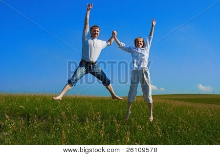 couple jumping in field under blue sky