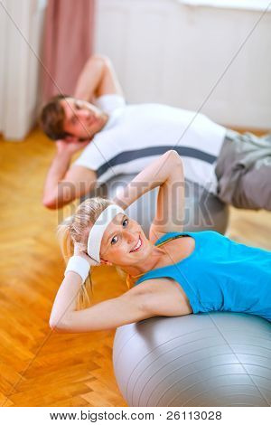 Healthy Couple Making Abdominal Crunch On Fitness Ball