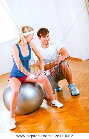 Smiling Personal Trainer Helping His Client