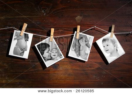Pictures of a newborn and mother attach to rope with clothes spins on wooden background