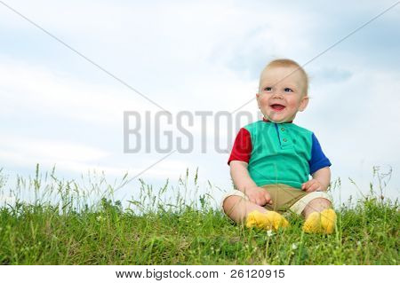 little baby sit on green grass under sky