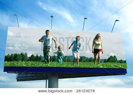 happy family run on grass in big billboard