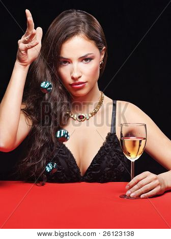 pretty young woman throwing dices on red table