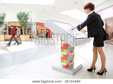 young business woman select 	goods on interactive display