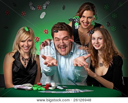 Poker players in casino with cards and chips on green background