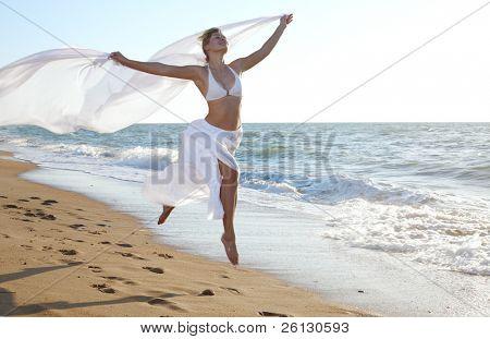 Постер, плакат: Женщина прыжки на пляже моря, холст на подрамнике
