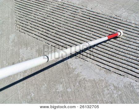 White cane touching ridges on a curb