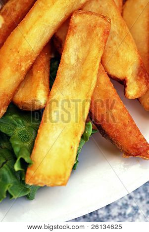 Close-up of a pile of golden French fries on a plate with lettuce