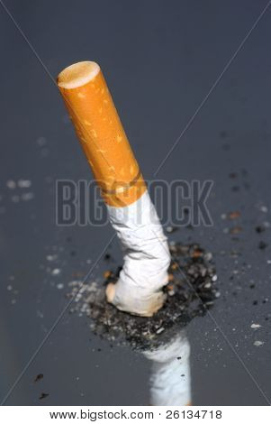 Cigarette butt standing up in pile of ash