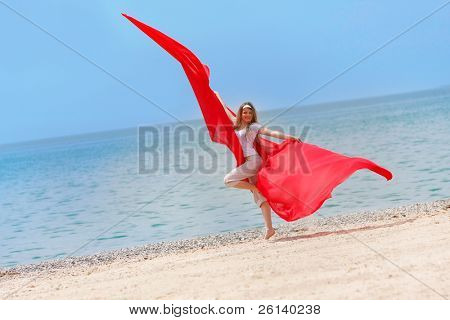 young happy girl with red wings jumping on beach