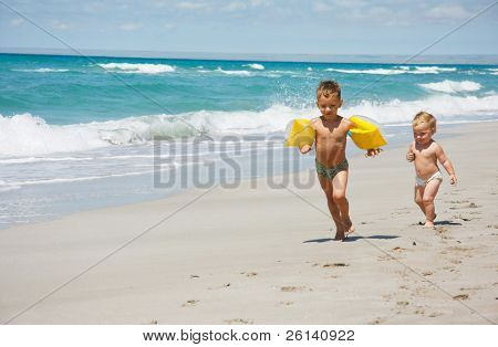 two kids running on beach