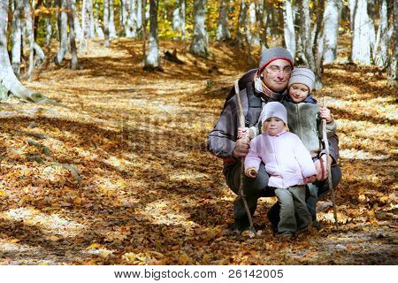 father and two kids in autumn forest