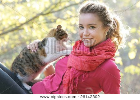 attractive girl with cat on natural background