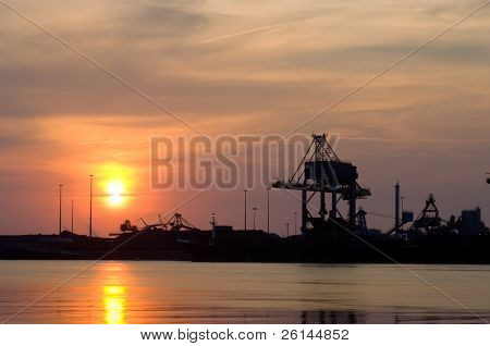Steelworks at sunset with a huge crane used to unload the raw materials, such as iron ore and coal