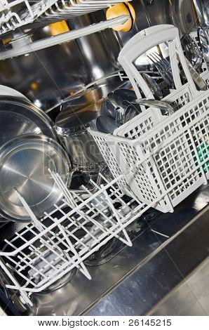 The interior of a dishwasher, with pots, pans, dish ware and cutlery.