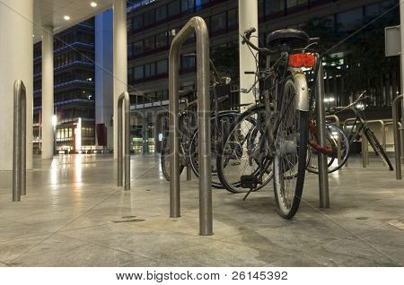 Bikes parked outside one of the ministries in the Hague, the Netherlands at night, one with a flat tire