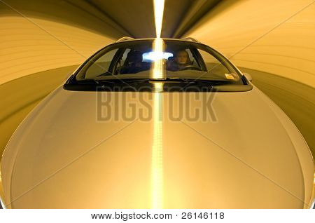 A car driving through a tunnel, seen from the hood, with the driver behind the wheel. A long exposure