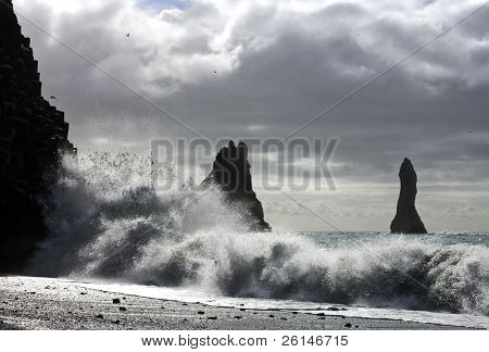 The waves of the Atlantic Ocean hitting the basalt and volcanic beaches of Iceland's south coast at Reynir, famous for it's troll-like landmasses, erecting out from the ocean