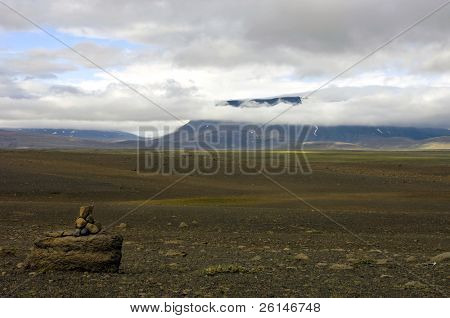 The vast, barren tundra landscape of the Sprengisandur Highland Road in Iceland, with the huge Vatnajokull volcanic glacier visible through the clouds.