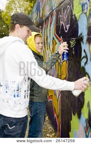 Two boys spray painting a stone wall outdoors.