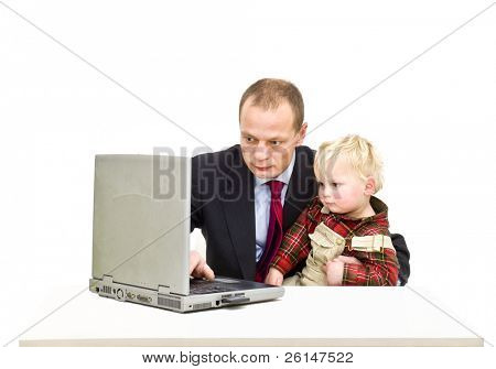 A father working on his laptop (can also be interpreted as playing) whilst caring for his toddler son