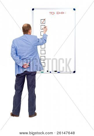 A business man checking off his completed tasks from a to do list, written on a whiteboard