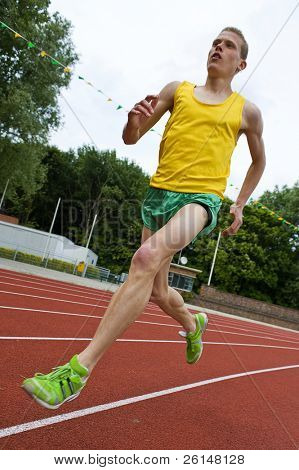 Running athlete on a middle distance race on an oval track in mid-air