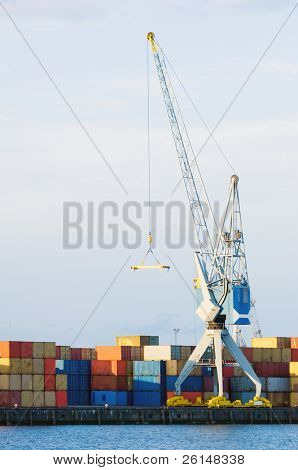 A large cargo crane stands at port in front of stacks of containers. There is no one viewable in the image. Vertically framed shot.