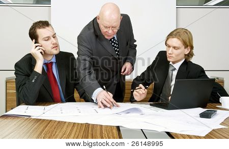 Two colleagues in a meeting on an architectural design with an interfering boss behind them