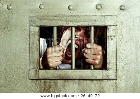Cross-processed image of a man going insane, grabbing the bars of his jail cell, looking rabid and screaming uncontrollably