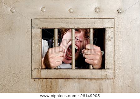 Man in prison going insane, grabbing the bars of his jail cell, looking rabid and screaming uncontrollably