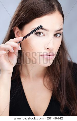 Pretty woman combing her eyebrow
