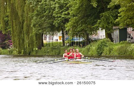 A coxed four on a canal at full speed