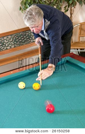 Senior man playing carambole billiards - slight motion blur in the red and yellow billiard balls