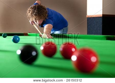 Snooker player taking a long shot across the table