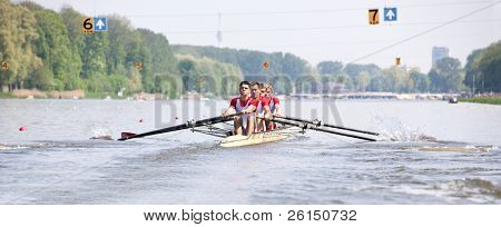 Four oarsmen in a coxed boat during a rowing regatta at full speed after the start